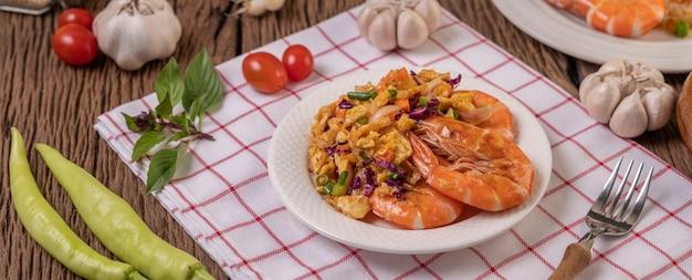 Crevettes frites aux œufs dans une assiette blanche posée sur un chiffon avec une fourchette.