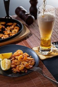 Crevettes frites et citron dans une assiette noire avec un verre de bière