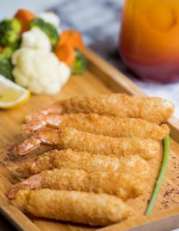 Crevettes frites croustillantes servies avec des légumes bouillis