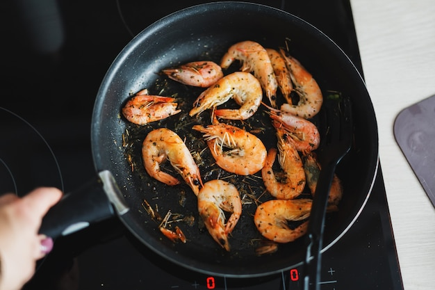 Crevettes frites dans l'huile sur poêle avec des épices. fermer