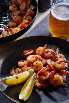Crevettes frites dans une poêle avec de l'ail et du citron sur une plaque noire et un verre de bière