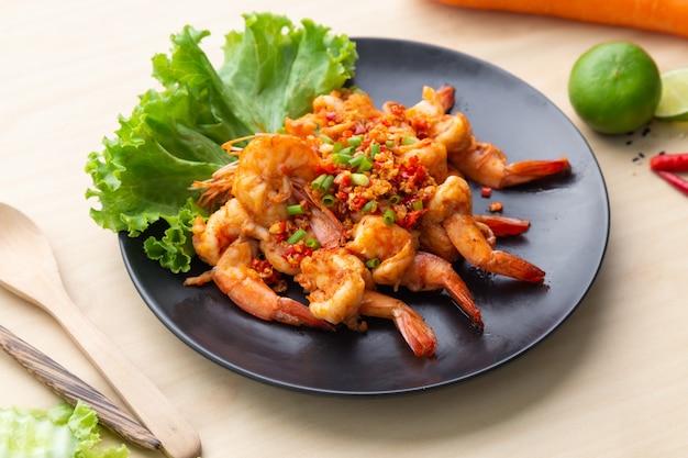 Crevettes frites avec du poivre et du sel dans une assiette noire sur une table en bois