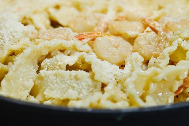 Crevettes frites avec pâtes italiennes et parmesan dans une casserole.