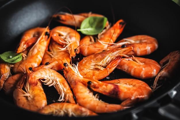 Crevettes frites avec sauce sur la poêle. fermer.