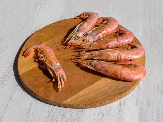 Crevettes géantes fraîches cuites sur une planche à découper en bois