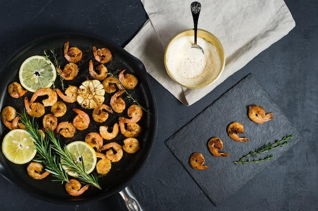 Crevettes géantes frites dans une poêle avec un bol de sauce.