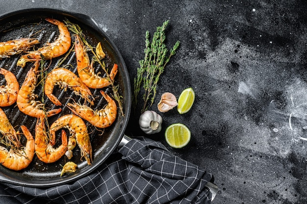 Crevettes géantes grillées, crevettes à l'ail, citron, épices à la poêle. fond noir