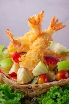 Crevettes géantes tempura avec salade et trempette de salsa sur une assiette blanche