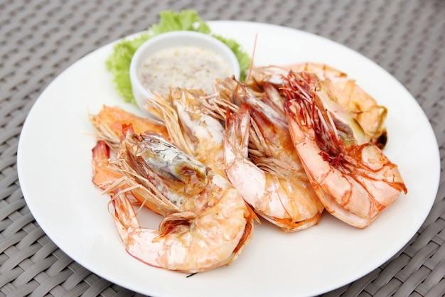 Crevettes grillé avec sauce de fruits de mer sur assiette blanche