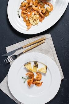 Crevettes grillées sur une assiette blanche à l'ananas.