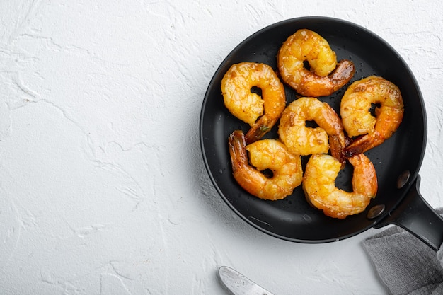 Crevettes grillées au miel et au soja, sur une poêle à frire, sur blanc