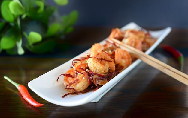 Crevettes grillées aux oignons et chili sur une plaque blanche