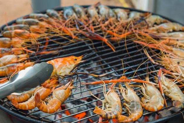 Crevettes grillées sur un cadre en acier avec feu chaud