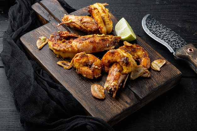 Crevettes grillées ou crevettes servies avec chutney de mangue ail croustillant, sur planche de bois, sur table en bois noir