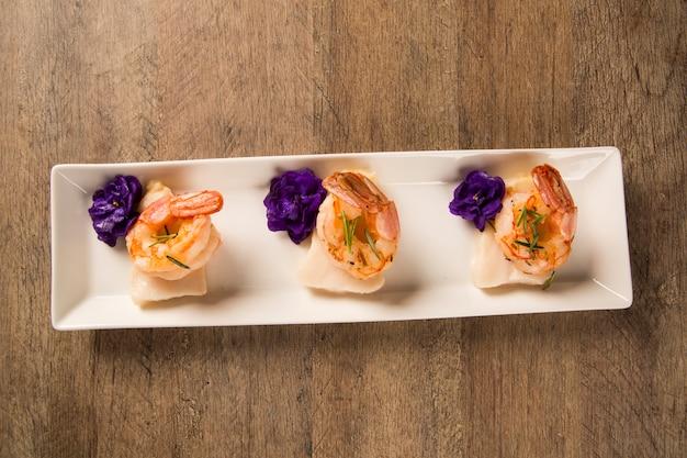 Crevettes grillées avec du poisson cru sur une plaque blanche à table