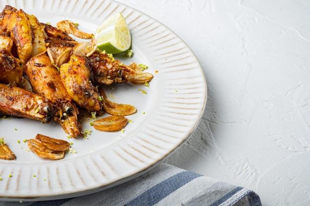 Crevettes grillées à la mangue ou jeu de crevettes, sur assiette, sur blanc