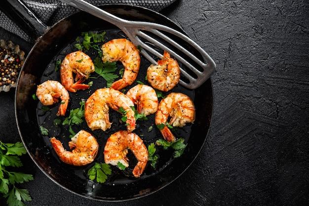 Crevettes grillées sur pan sur fond sombre