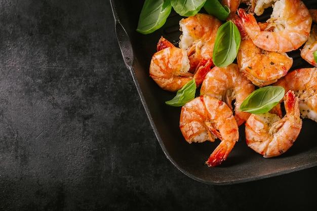 Crevettes grillées sur pan sur table sombre