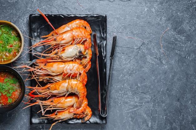 Crevettes grillées sur plaque noire avec sauce épicée sur table.