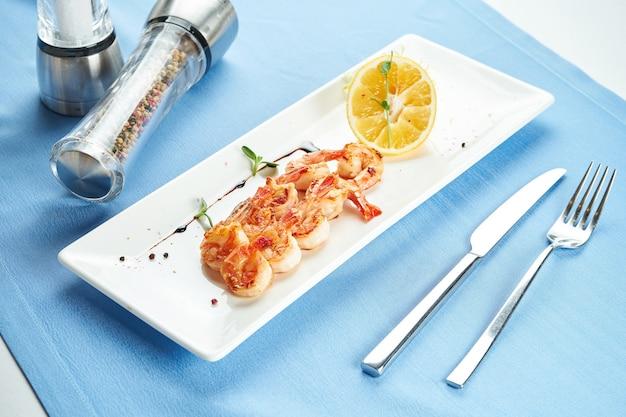 Crevettes méditerranéennes grillées appétissantes au citron dans une assiette blanche sur une nappe bleue