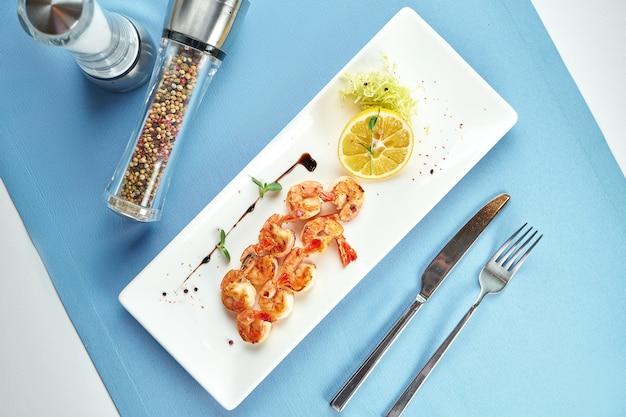 Crevettes méditerranéennes grillées appétissantes au citron dans une assiette blanche sur nappe bleue
