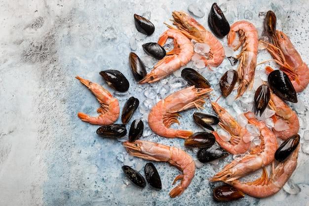 Crevettes et moules crues avec de la glace sur fond bleu