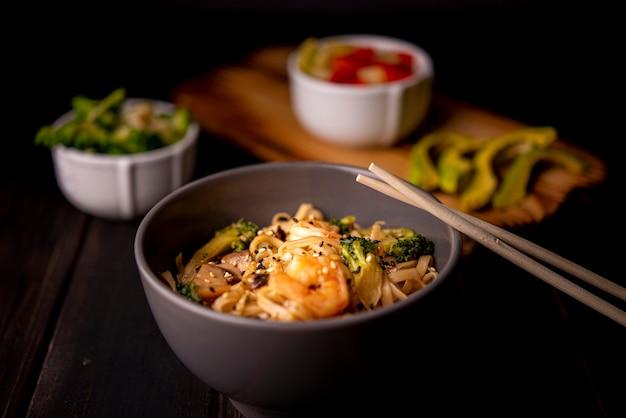 Crevettes sur nouilles dans un bol avec avocat et baguettes