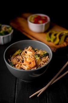 Crevettes et nouilles dans un bol avec des baguettes
