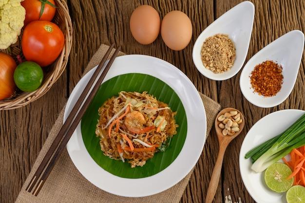 Crevettes padthai dans un bol noir avec des œufs, de l'oignon de printemps et de l'assaisonnement sur une table en bois.