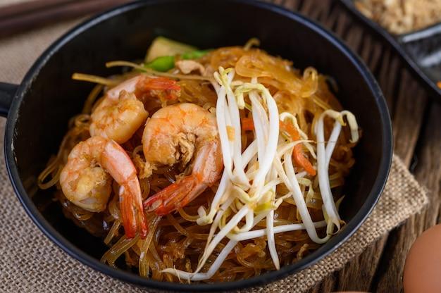 Crevettes padthai dans un bol noir.