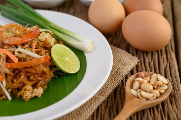 Crevettes padthai dans un plat blanc avec de la chaux et des œufs sur une table en bois.