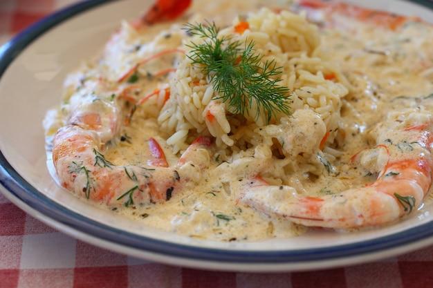 Crevettes avec paella de riz ou risotto ou jambalaya avec sauce blanche sur une assiette.