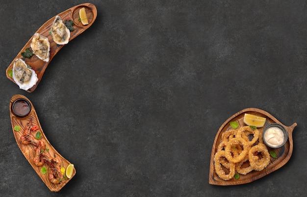 Crevettes rapana calmar anneaux en pâte sur les planches sur fond gris horizontal avec place pour le texte vue de dessus