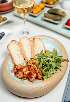 Crevettes à la roquette et pain servis avec du vin blanc