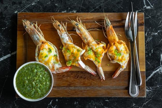 Crevettes rôties au fromage et sauce sur planche de bois