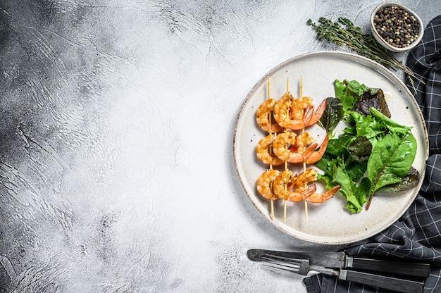 Crevettes rôties en brochettes avec salade d'épinards