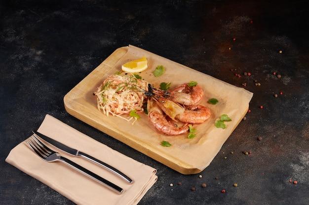 Crevettes rouges bouillies fraîches aux épices sur plaque sur fond sombre