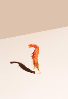 Crevettes rouges sur fond beige. concept minimaliste dans un style isométrique