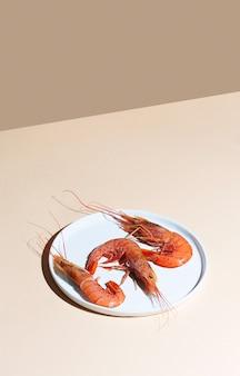 Crevettes rouges sur une plaque blanche et fond beige. concept minimaliste dans un style isométrique
