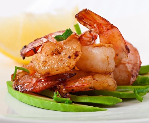 Crevettes sautées à l'ail et à la sauce soja sur un coussin de tranches d'avocat
