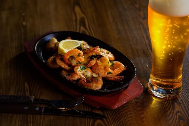 Crevettes sautées avec du jus de citron et de rosmarine fraîches et un verre de bière