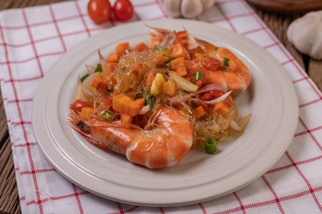 Crevettes sautées avec des nouilles en verre dans une assiette blanche posée sur un chiffon avec des œufs et de l'ail.