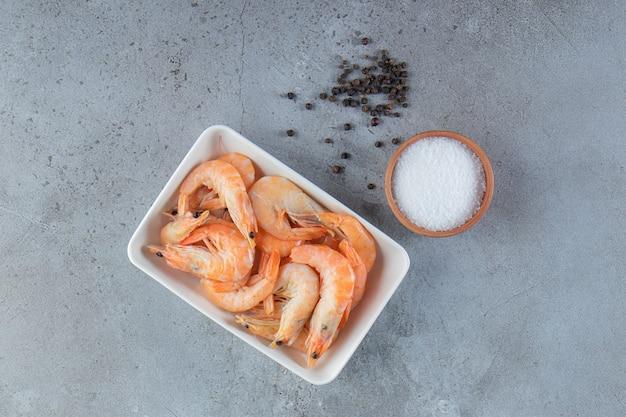 Crevettes savoureuses dans un bol à côté de sel et d'épices, sur la surface en marbre.