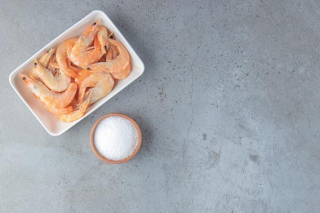 Crevettes savoureuses dans un bol à côté de sel, sur fond de marbre.