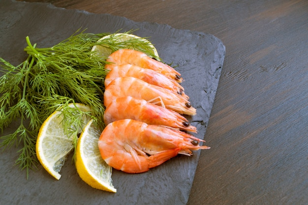 Crevettes sur un tableau noir avec citron et aneth.