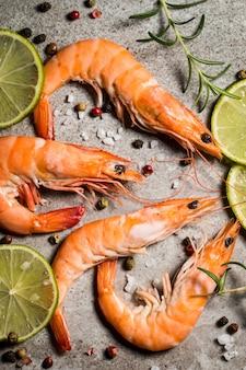 Crevettes tigrées au citron vert, citron, romarin et épices au poivre noir sur pierre. crevettes fraîches et savoureuses prêtes à être cuites.