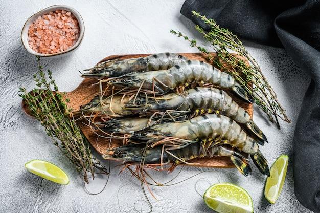 Crevettes tigrées crues noires, crevettes sur une planche à découper