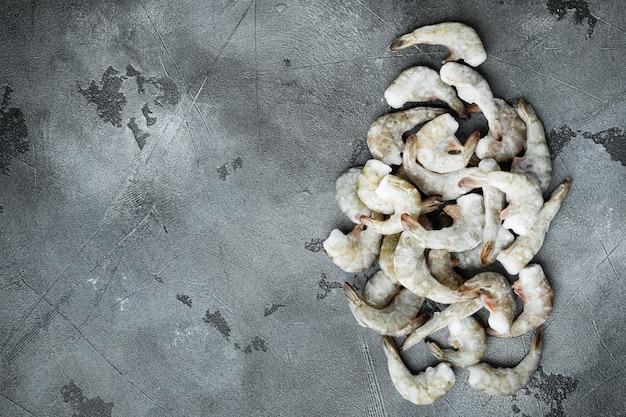 Crevettes tigrées crues non cuites surgelées, ensemble de crevettes, sur fond de pierre grise, vue de dessus à plat, avec espace de copie pour le texte
