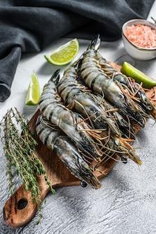 Crevettes tigrées fraîches, crevettes aux épices et herbes sur une planche à découper.