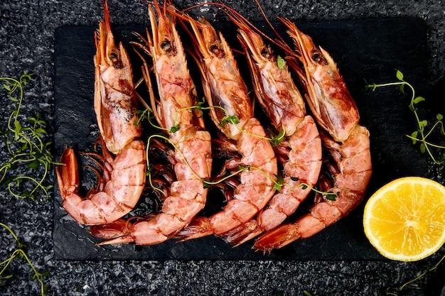 Crevettes tigrées grillées sur une plaque d'ardoise noire